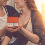 Baufinanzierung: Ein junges Paar hält ein Modellhaus in den Händen
