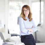 Beamtendarlehen: Einen freundliche Frau mit Brille lehnt am Tisch