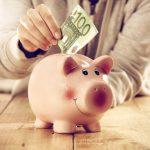 Konsumdarlehen: Eine Hand steckt einen Geldschein in ein Sparschwein