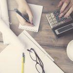 Schufafreie Darlehen: Frauenhände mit Stift und Tischrechner