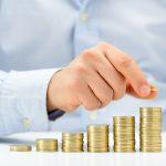 Umschuldung: Eine Männerhand stapelt Kleingeld